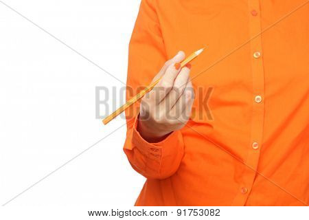 Female hand in orange sleeve holding a pencil
