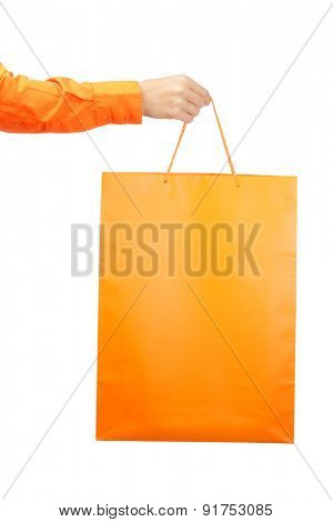 Female hands holding an orange shopping bag.
