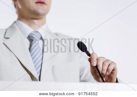 Young businessman standing on stage and speaking to microphone