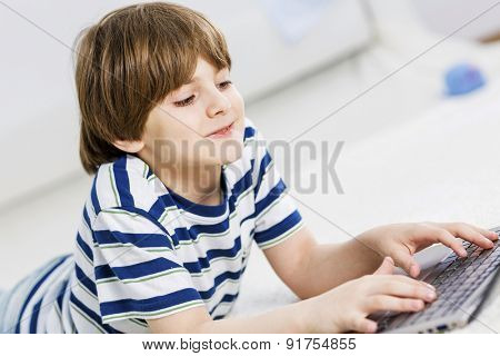 Cute boy lying on floor and using laptop