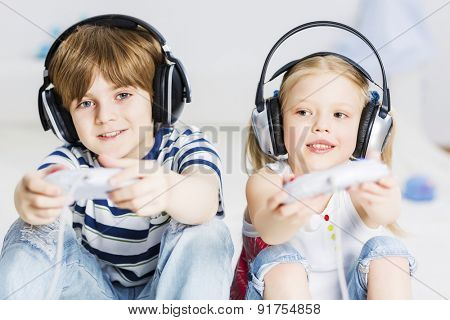 Cute boy and girl playing game in wireless headphones