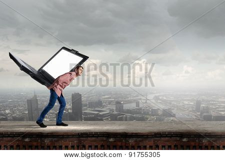 Young man in casual carrying big laptop on back