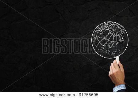 Close up of hand drawing globe on blackboard