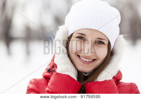 The beautiful smiling woman on walk in winter wood