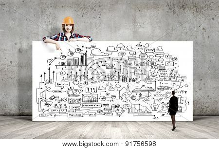 Young woman builder wearing helmet and holding banner with business plan