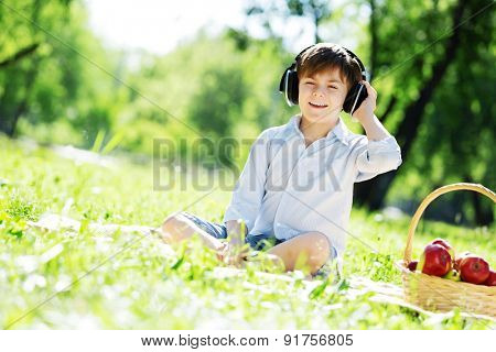 Young joyful boy in summer park wearing headphones