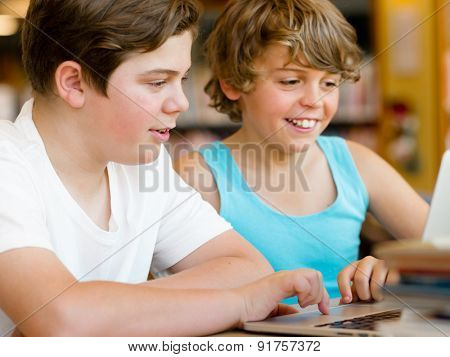 Two boys in library with notebook