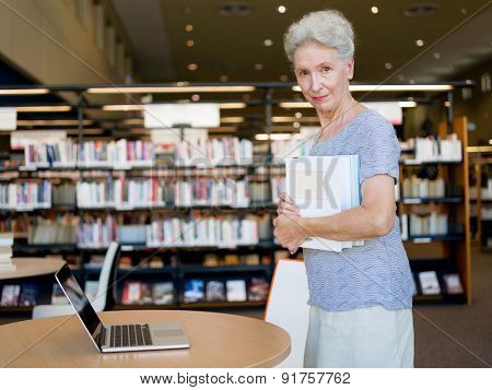 Elderly lady standing next to table with laptop