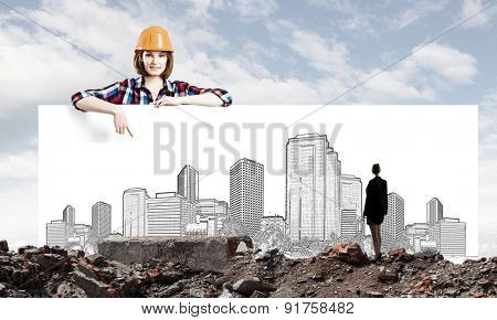 Young woman builder wearing helmet and holding banner with construction project