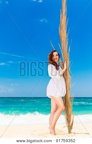 Happy Young Brunette In White Dress Sianding With Palm Leaves On A Tropical Beach.