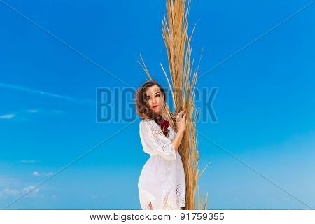 Happy Young Brunette In White Dress Sianding With Palm Leaves On A Tropical Beach. Summer Vacation C