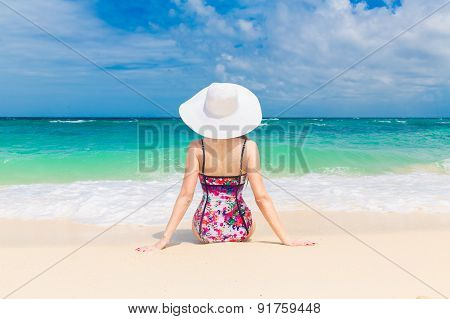 Young Beautiful Girl In A Straw White Hat Back To The Viewer On The Beach Of A Tropical Island. Summ