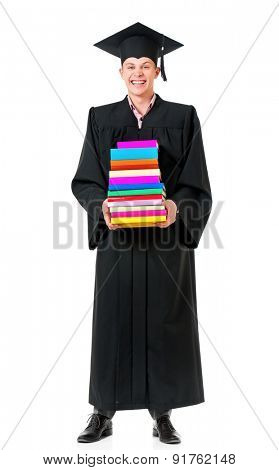 Cheerful graduate guy student in mantle with books, isolated on white background