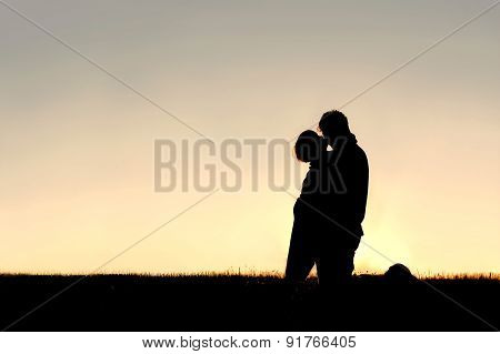 Silhouette Of Young Child Kissing Father On Cheek