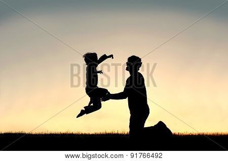 Silhouette Of Child Jumping Into Happy Father's Arms