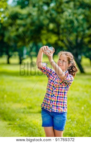 Lovely Teenage Girl Taking Picture With Smartphone In Sunny Day In Summer Park