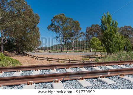 Railroad Tracks Pass A Park With Fence