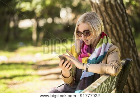 Young fashionable woman uses smartphone sitting on bench in the Park.