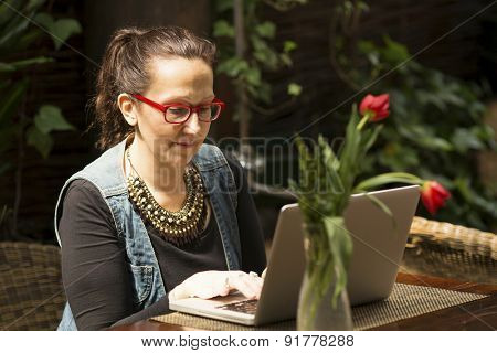 Young woman with laptop in the outdoor summer cafe.