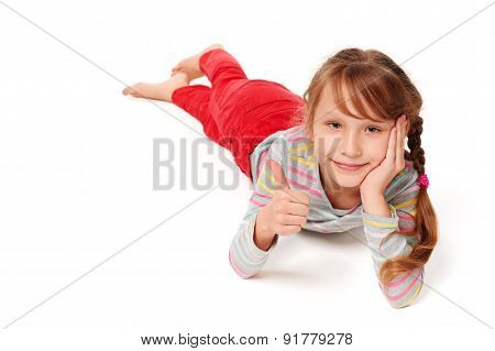 Front view of smiling child girl lying on stomach