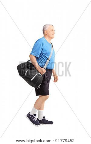 Full length portrait of a senior man in sportswear carrying a sports bag and walking isolated on white background