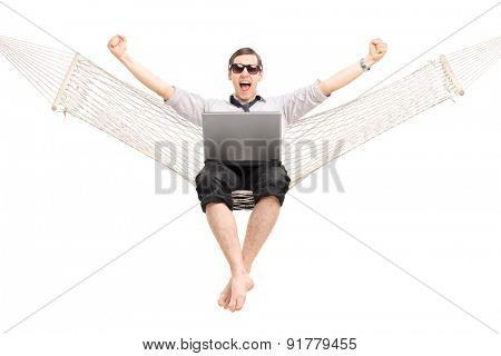 Delighted businessman working on laptop and gesturing success seated in a hammock isolated on white background
