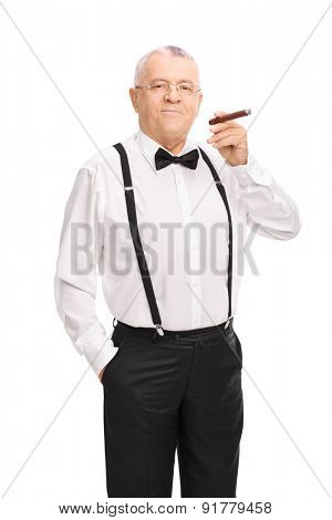 Vertical shot of an elegant senior gentleman smoking a cigar and looking at the camera  isolated on white background