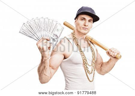 Thug with gold chain around his neck holding a baseball bat and a stack of money isolated on white background