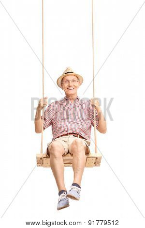 Vertical shot of a playful senior swinging on a swing and looking at the camera isolated on white background
