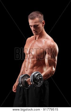 Vertical shot of a muscular male bodybuilder working out with a weight on black background