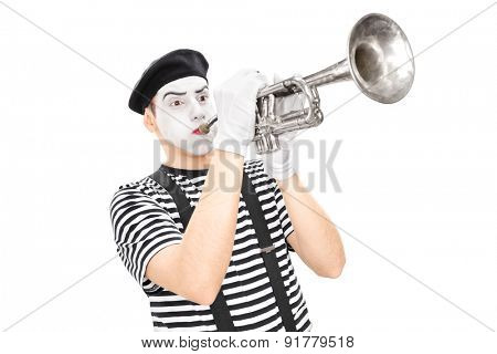 Studio shot of a young male mime artist playing a trumpet isolated on white background