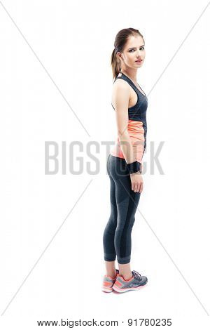 Full length portrait of a fitness woman standing isolated on a white background and looking at camera
