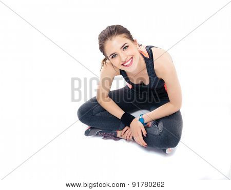 Smiling pretty woman sitting on the floor in sports wear. Isolated on a white background. Looking at camera