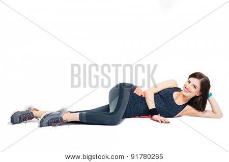 Happy fitness woman lying on the floor isolated on a white background. Looking at camera