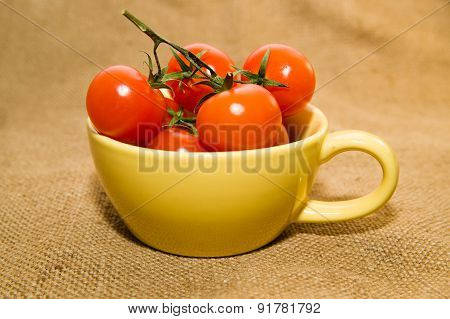 Red Cherry Tomatoes In A Yellow Cup On Old Cloth
