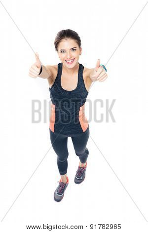 Full length portrait of a happy fitness woman showing thumbs up isolated on a white background. Looking at camera