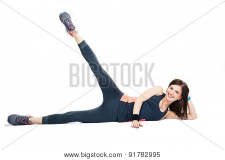 Happy sporty woman doing stretching exercise isolated on a white backgorund. Looking at camera