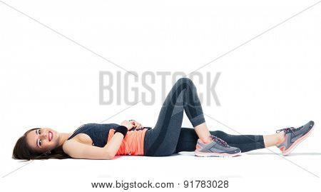 Cheerful sporty woman lying on the floor isolated on a white background. Looking at camera