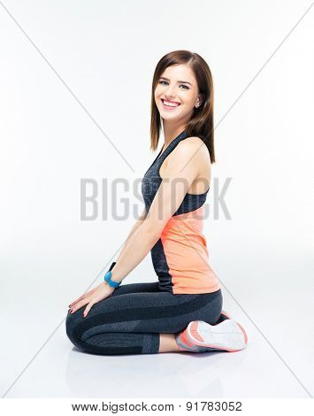 Smiling sporty woman sitting on the floor isolated on a white background. Looking at camera