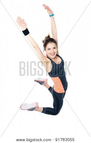 Happy sporty woman jumping isolated on a white background and looking at camera