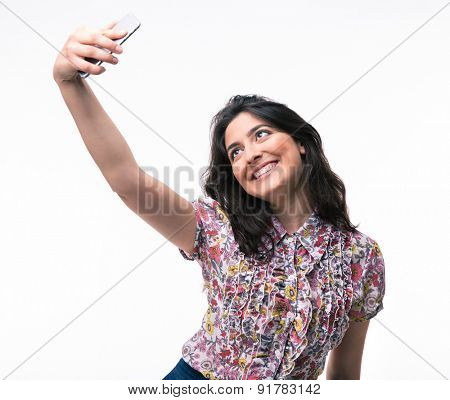 Young woman making selfie photo on smartphone isolated on a white background