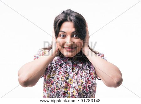 Happy woman closed her ears with hands and looking at camera isolated on a white background
