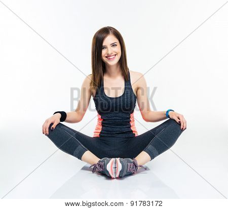 Happy fitness woman sitting on the floor isolated on a white background. Looking at camera
