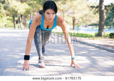 Sporty woman runner in start position outdoors in park