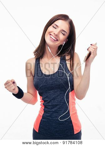 Happy sporty woman listening music in headphones isolated on a white background