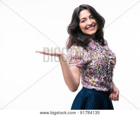 Smiling woman presenting copy space on her palm isolated on a white background. Looking at camera