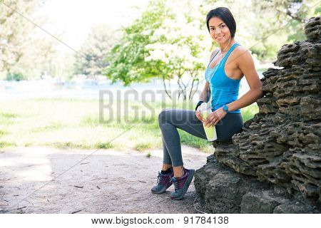 Portrait of a fitness woman holding bottle with water and resting outdoors in park