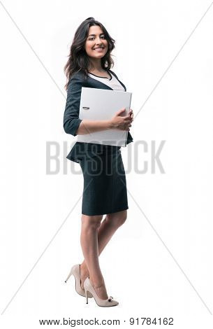 Full length portrait of a happy businesswoman standing and holding folder isolated on a white background. Looking at camera