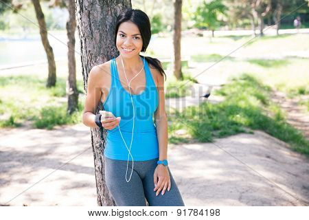 Happy sporty woman standing with smartphone and headphones outdoors in park
