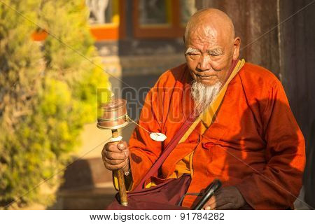 KATHMANDU, NEPAL - CIRCA DEC, 2013: Unidentified Buddhist monk near stupa Boudhanath. Stupa is one of the largest in the world, of 1979 is a UNESCO World Heritage Site.
